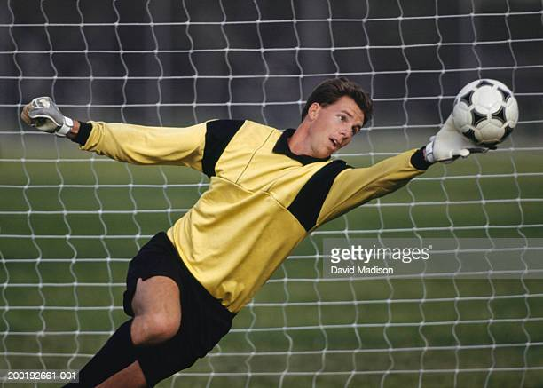 Young male goalie reaching for soccer ball