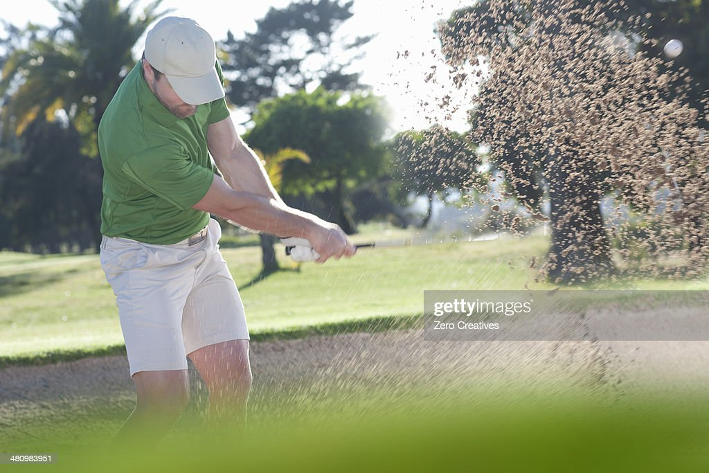 Young male golfer playing out of bunker