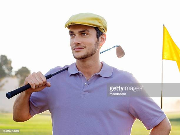 Young male golfer standing on course, holding club on shoulder, portrait