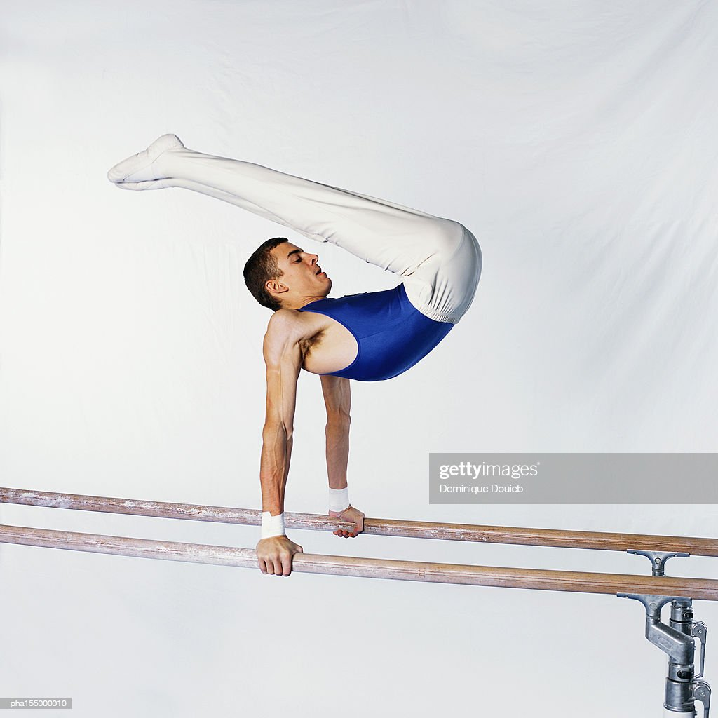Young male gymnast on parallel bars, side view.
