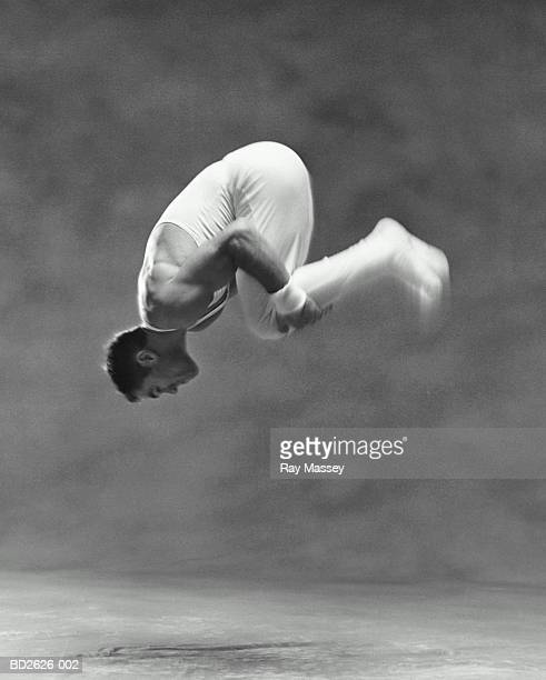 Young male gymnast performing somersault (blurred motion, B&W)