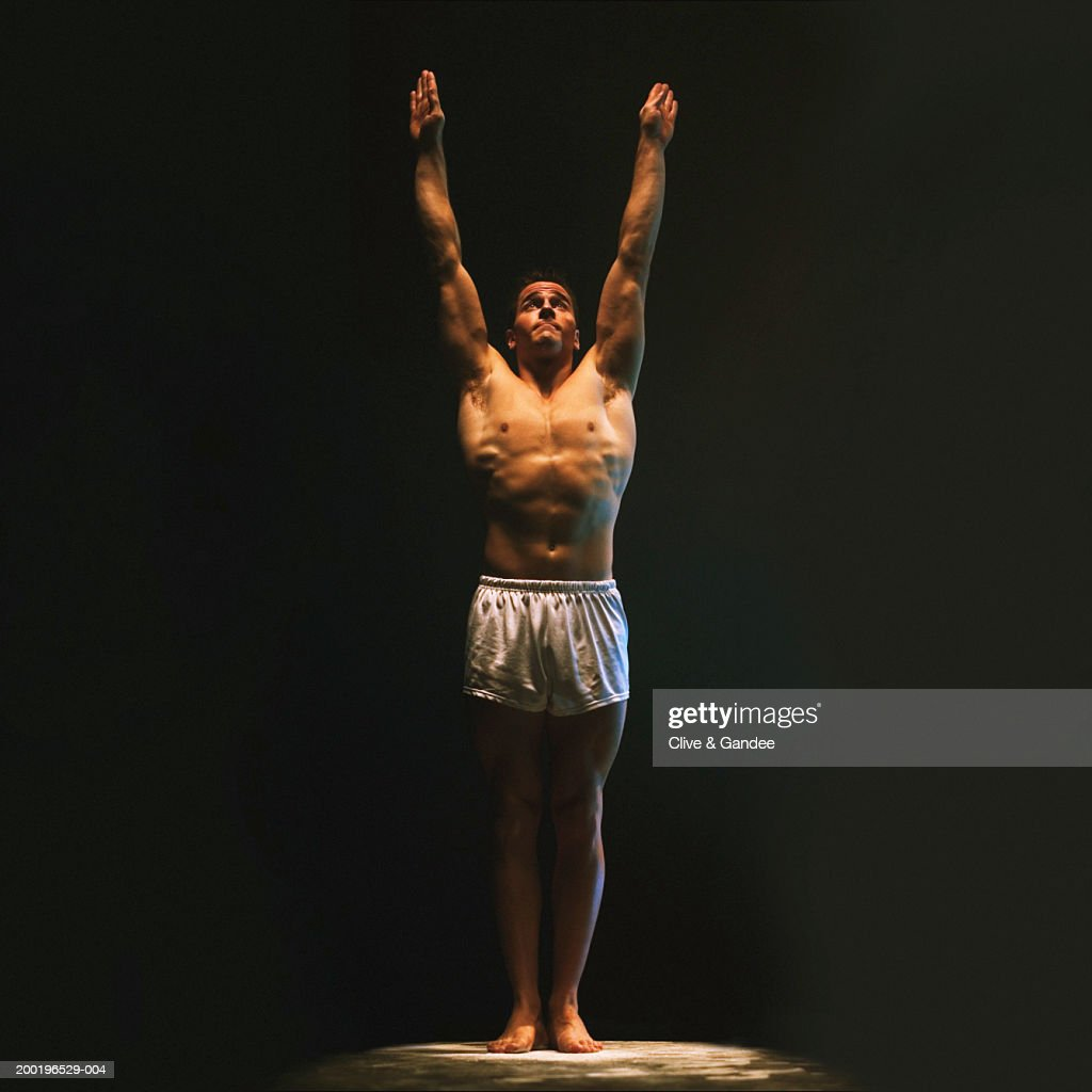 Young male gymnast with arms raised : Stock Photo