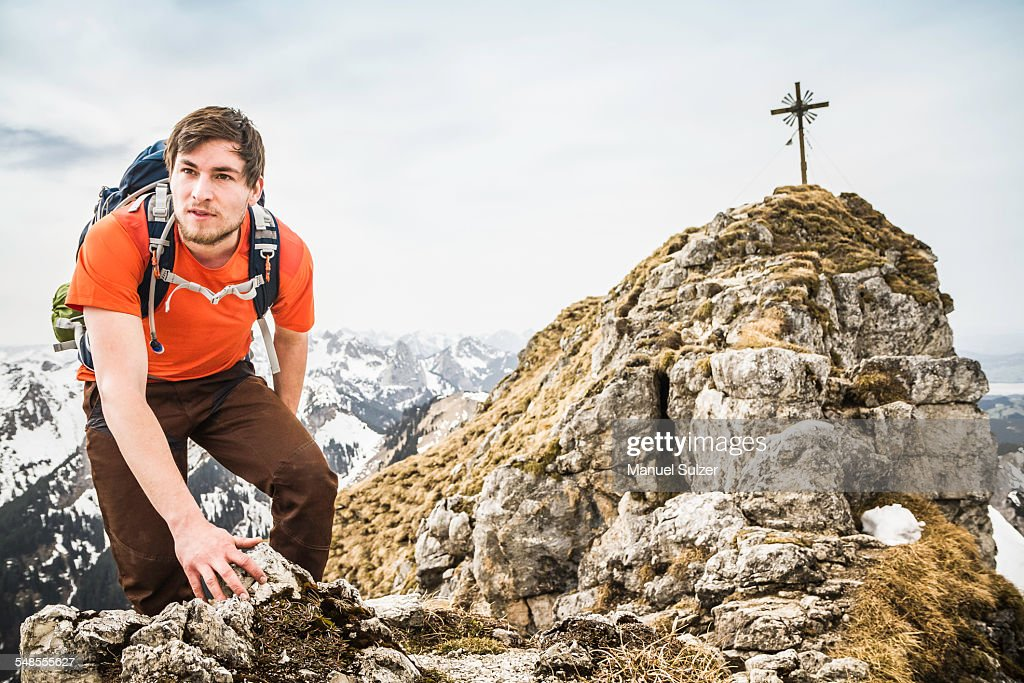 Young male hiker climbing on peak of Klammspitze mountain, Oberammergau, Bavaria, Germany : ストックフォト