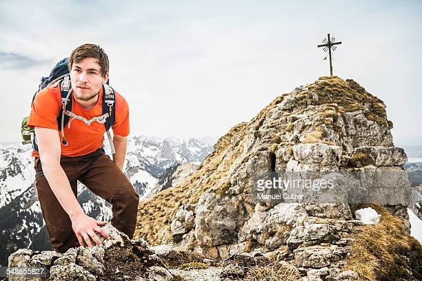 Young male hiker climbing on peak of Klammspitze mountain, Oberammergau, Bavaria, Germany