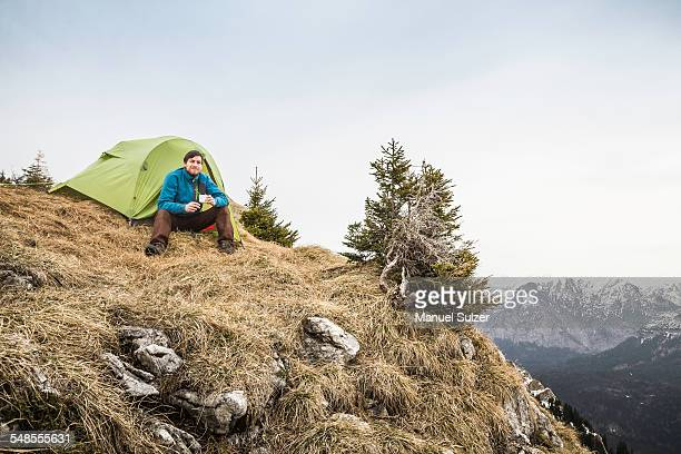 Young male hiker drinking coffee in front of tent on Klammspitze mountain, Oberammergau, Bavaria, Germany