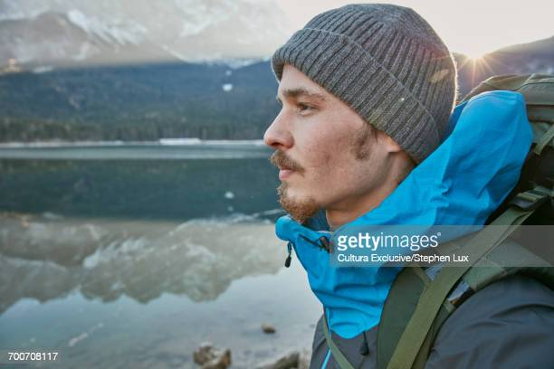 Young male hiker in knit hat looking out to Lake Eibsee in winter, Zugspitze, Bavaria, Germany