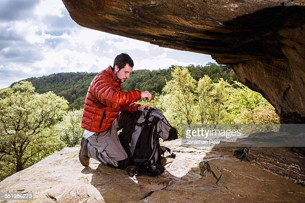 Young male hiker unpacking backpack on crocodile rock, Pateley Bridge, Nidderdale, Yorkshire Dales