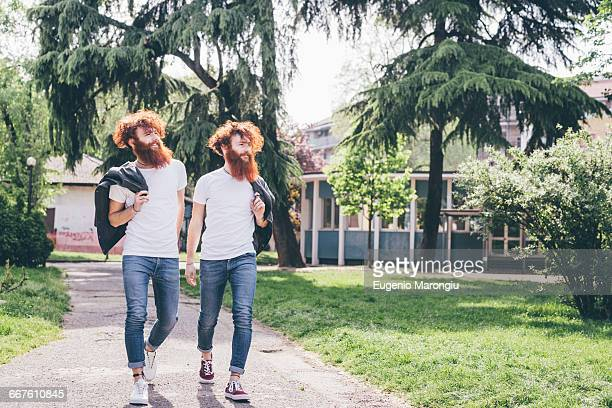 Young male hipster twins with red beards strolling in park
