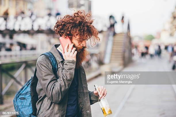 Young male hipster with red hair and beard chatting on smartphone on city street