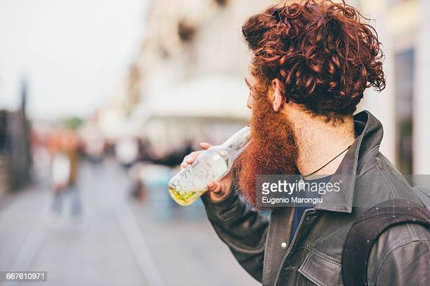 Young male hipster with red hair and beard drinking bottled beer on city street