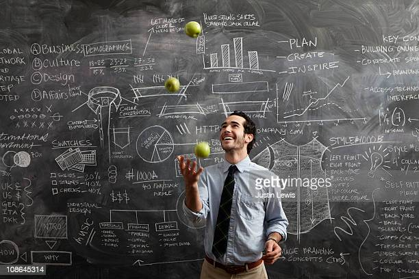 young male in front of chalkboard juggling apples