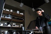 Young male in music shop. Vinyl records buying. Audio listening in headphones, modern lifestyle