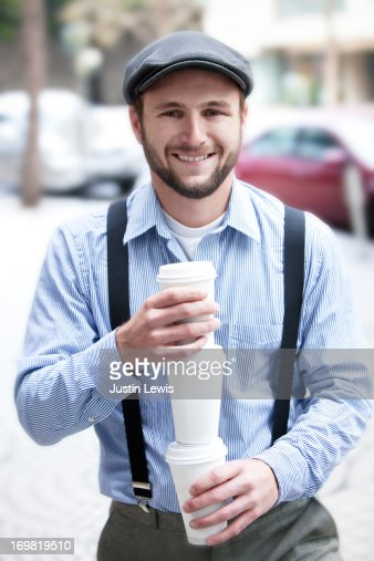Young male in smiling with staked cups of coffee