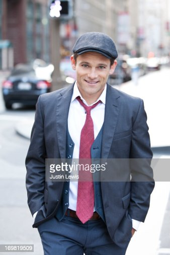 Young male in suit smiling on street in the city