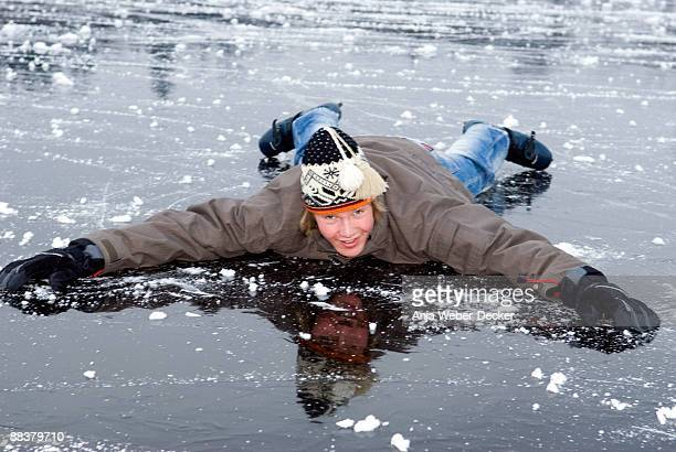 Teenage boy (18-19) in winter clothes lying on frozen lake, smiling, portrait