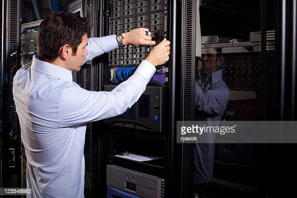 Young Male IT Technician Reparing Data Drives on Server Panel