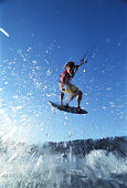 Young male kiteboarder in mid-air, low angle view (blurred motion)