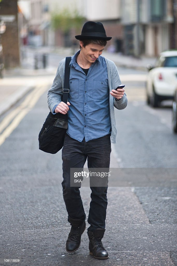 Young male looking at mobile phone : Stock Photo