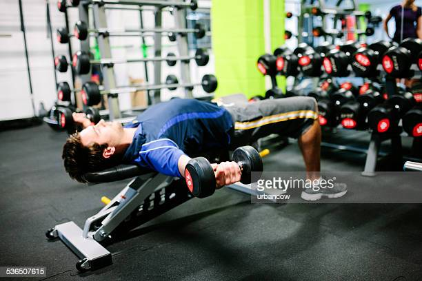 Young male lying on an exercise bench, using dumbbells