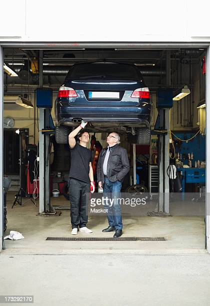 Young male mechanic and customer discussing underneath car at auto repair shop