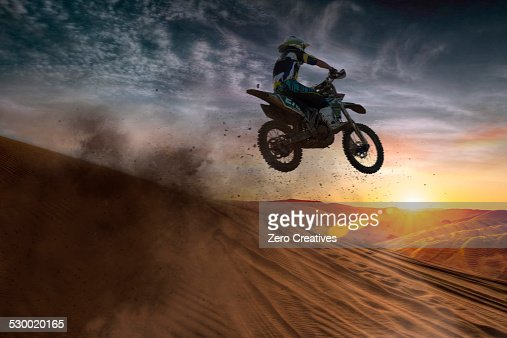 Young male motocross racer jumping mid air at sunset