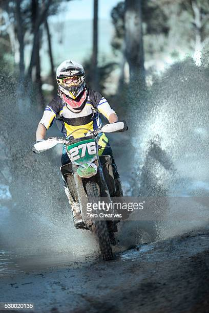 Young male motocross racer splashing through forest puddle