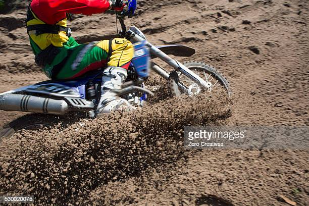 Young male motocross rider racing through mud track