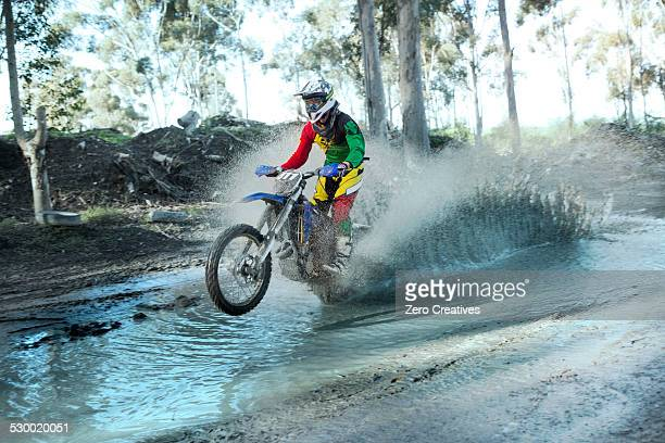 Young male motocross rider splashing through forest river