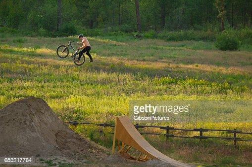 A young male mountain bike rider does a one-handed cannonball trick while riding a wooden ramp jump on a sunny day.. : Stockfoto