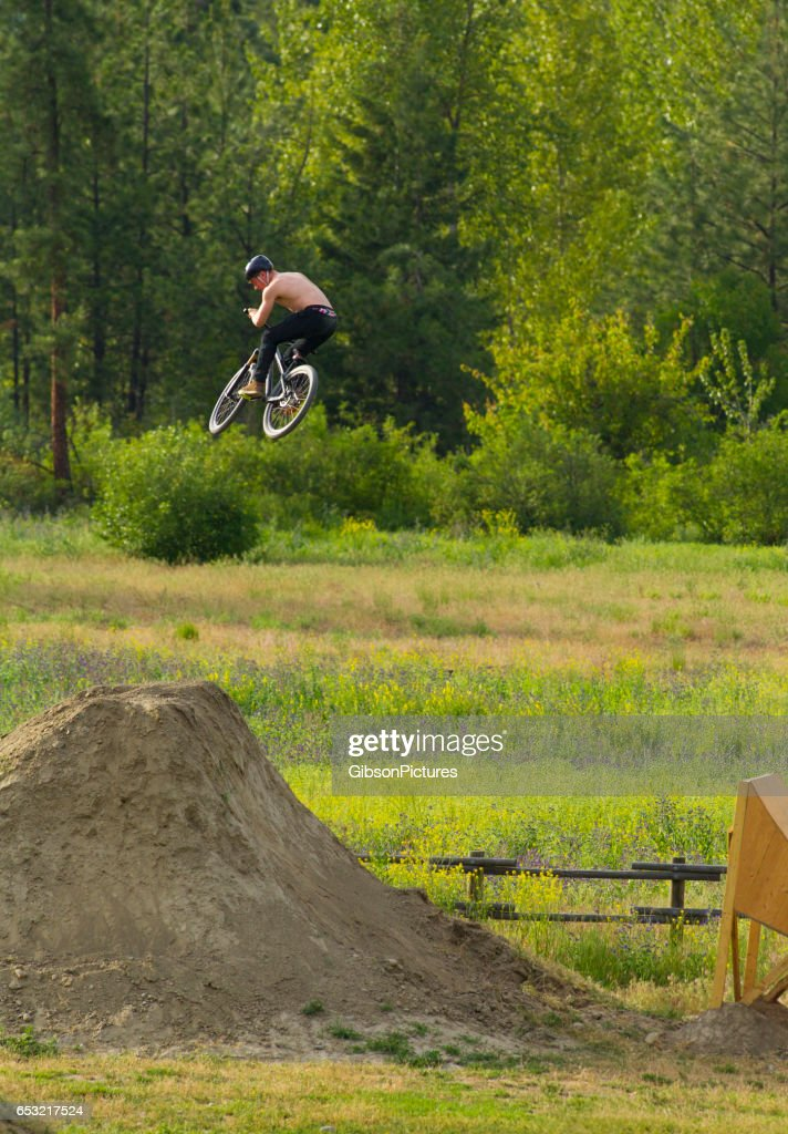 A young male mountain bike rider hits a big wooden ramp in the summertime. : Stock Photo