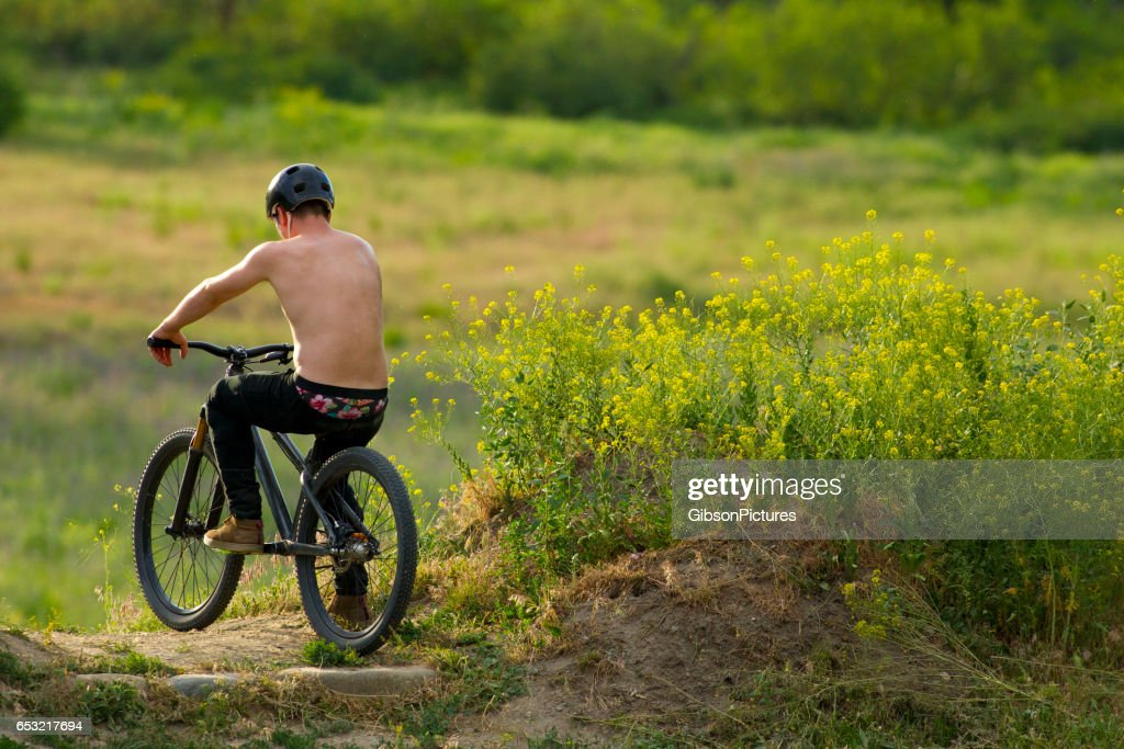 A young male mountain bike rider rests at the top of the hill before hitting a big jump in the summertime. : Stock Photo