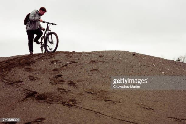 Young male mountain biker preparing to bike from quarry hill