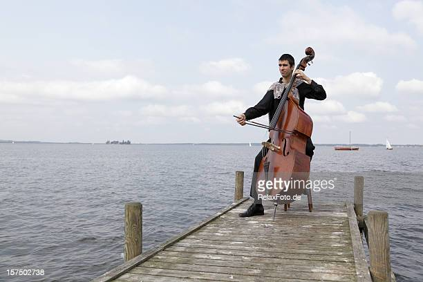 Young male musician playing double bass on lakeside jetty (XXXL)