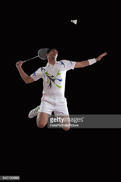 Young male player jumping to hit shuttlecock with racket over black background