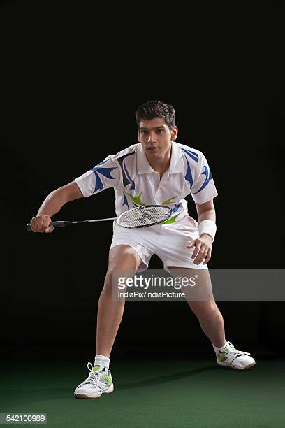 Young male player playing badminton over black background