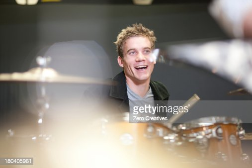 Young male playing drum kit in music store