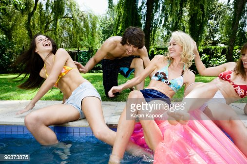 Young male pusing 3 young females into swimming po : Stock Photo