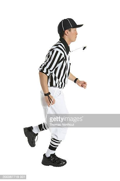 Young male referee running, side view