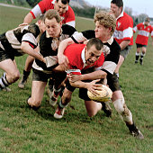 Young male rugby player being tackled by opponents