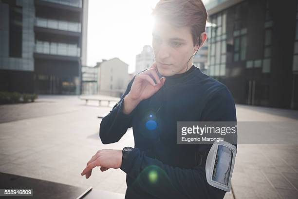 Young male runner checking neck pulse in city square