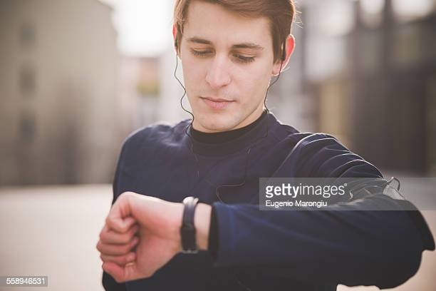 Young male runner checking wristwatch in city square