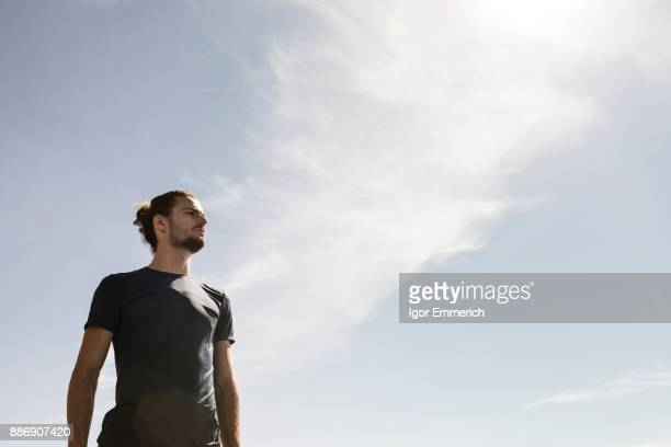 Young male runner gazing against blue sky