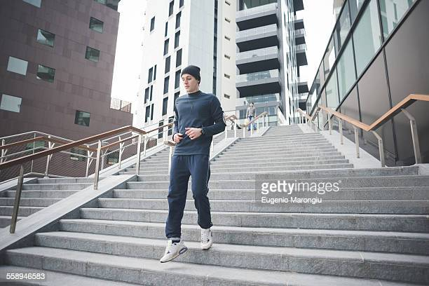 Young male runner running down city stairs