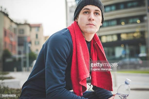 Young male runner taking a break in city