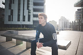 Young male runner taking a break on bench in city square