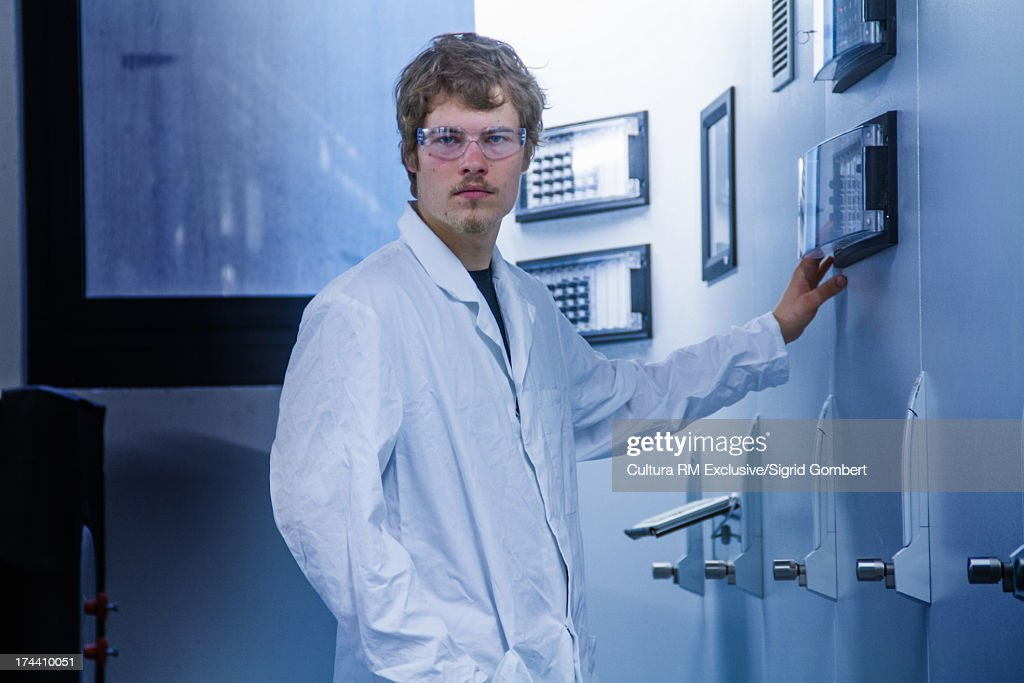 Young male scientist using control panel : Stock Photo