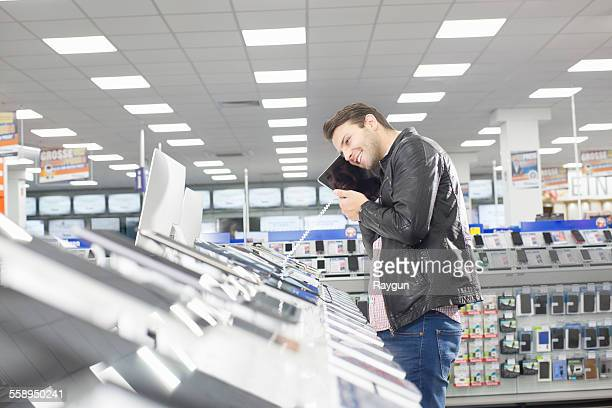 Young male shopper holding up chosen digital tablet in electronics store