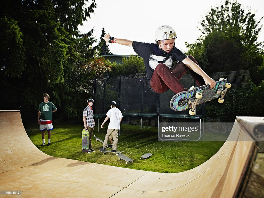 Young male skateboarder in mid air on halfpipe
