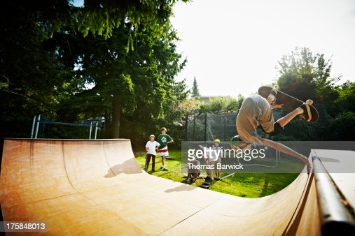 Young male skateboarder inverted on halfpipe