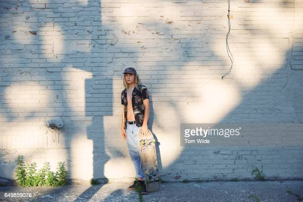 Young male skateboarder leaning against a brick wall with his skateboard